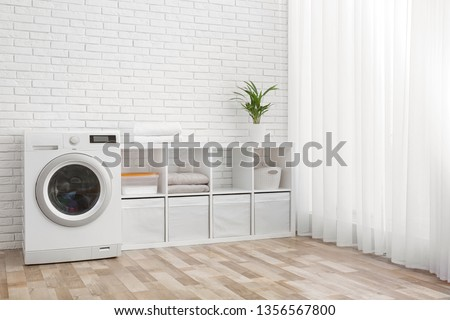 Modern washing machine near brick wall in laundry room interior, space for text #1356567800