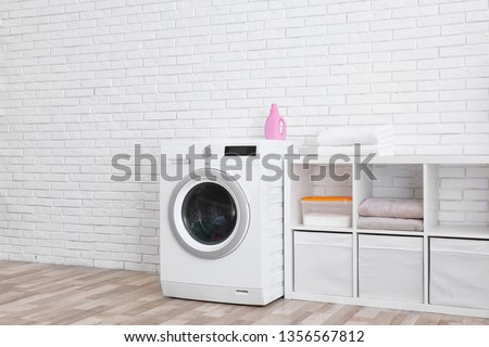 Modern washing machine near brick wall in laundry room interior, space for text #1356567812