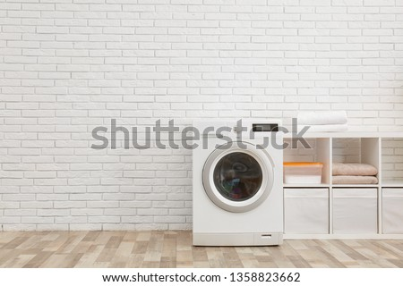 Modern washing machine near brick wall in laundry room interior, space for text #1358823662