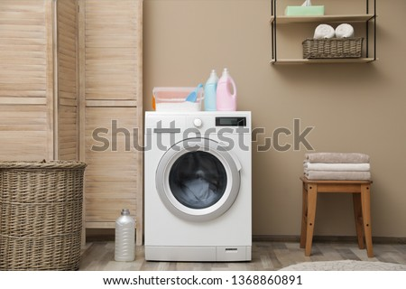 Modern washing machine near color wall in laundry room interior #1368860891