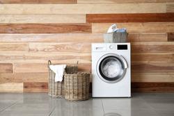 Modern washing machine with laundry near wooden wall