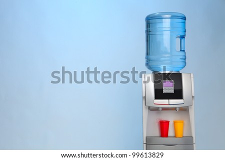 Modern water cooler on blue background with red and yellow plastic cups