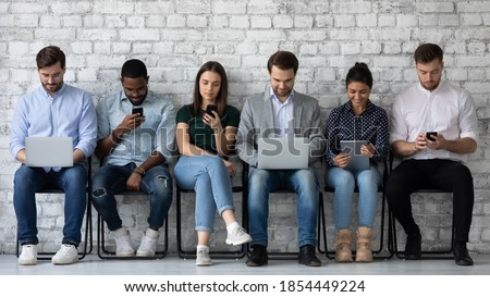 Modern way to communicate. Row of diverse young people sitting close to wall holding different gadgets cellphones laptops pads surfing internet chatting browsing social networks work or study online Сток-фото ©
