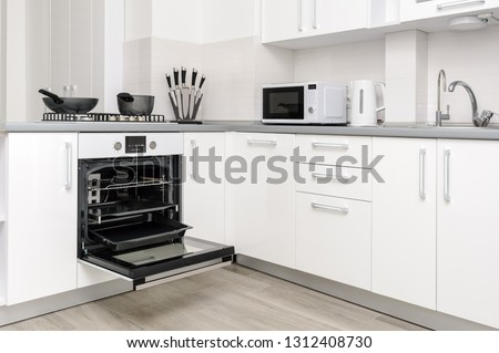 Modern white and black kitchen, gas stove, electric oven is open