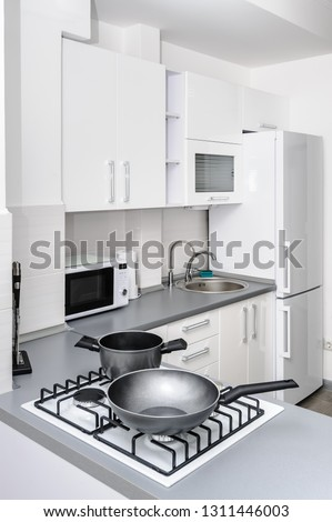 Modern white and black kitchen, gas stove with cooking pan, minimalistic clean design