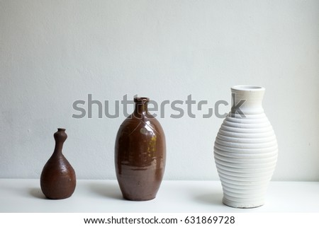 Modern white and brown tall ceramic vase with interior decor concept, decoration object on white background.