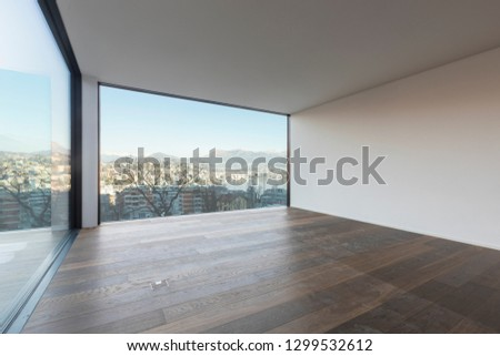 Modern white apartment with parquet floors and large windows overlooking the lake of Lugano. Nobody inside