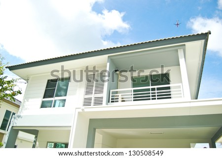 Modern white building with balcony on a blue sky