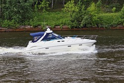 Modern white cabin awning plastic motor boat inboard motor floating left to right on calm water with keel water wake, side top view on summer day, family powerboat active recreation, watersports