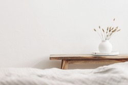 Modern white ceramic vase with dry Lagurus ovatus grass and marble tray on vintage wooden bench, table. Blurred beige linen blanket in front. Scandinavian interior. Empty white wall, copy space.