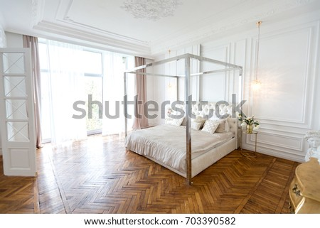 Modern white design interior in classical style of a spacious studio apartment with a huge four-poster bed, a wooden large shelf and a beautiful white sofa