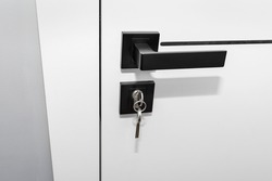 Modern white door with matte black handle and magnetic locks, lock with key inserted.