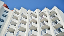Modern white facade of a residential building with large windows. View of modern designed concrete apartment building.