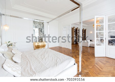 Modern white interior design in classical style of a spacious studio apartment with a huge bed & Modern white interior design in classical style of a spacious studio ...