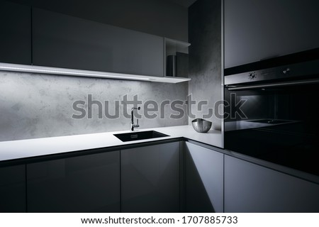 Modern white kitchen corner in minimalist design, during night, with light strip turned on, modern oven, granite sink, and premium materials such as glass, concrete, aluminum and stainless steel.