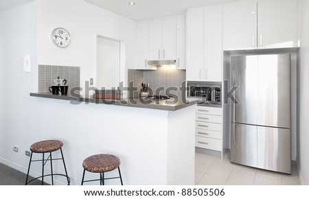 Modern white Kitchen in apartment with Polished Stainless Steel Appliances