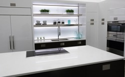 Modern white kitchen with quartz countertop, stainless cooktop,
