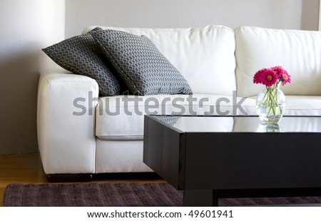modern white living room with vase of pink daisies