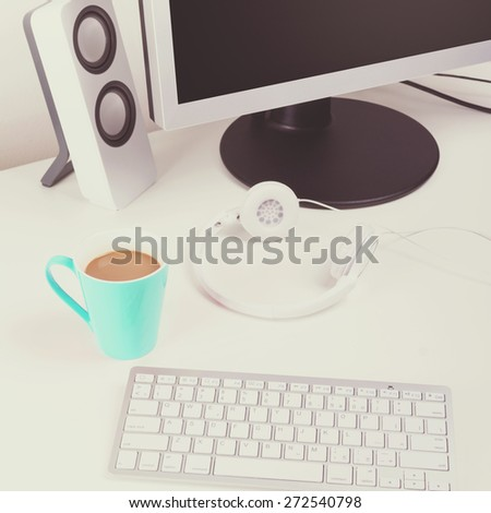 Modern white minimalist home office. Closeup of modern wireless keyboard, turquoise coffee cup, headphones, monitor and speakers. Square format, matte filter.