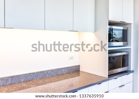 Modern white minimalist kitchen features cabinets with granite countertop and microwave toaster with empty space in office or home #1337635910