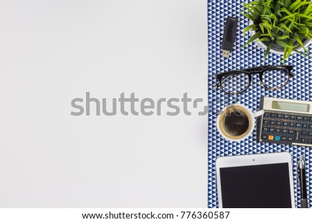Modern white office desk table with a tablet, calculator, pen, eyeglasses and cup of coffee. Top view with copy space, flat lay.