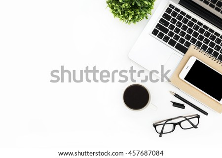 Modern white office desk table with laptop computer, smartphone with black screen over a notebook and cup of coffee. Top view with copy space, flat lay.