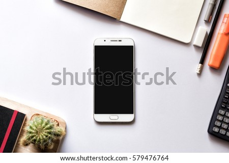Modern white office work table with smartphone mock up notebook pen and calculator top view  #579476764
