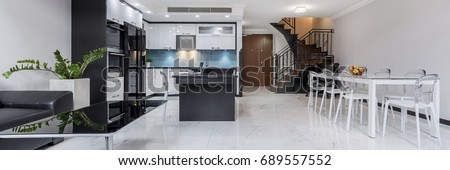 Modern, white, open plan apartment with gloss flooring, table, kitchen and staircase, panorama