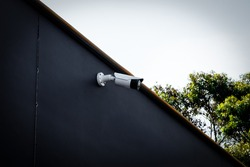Modern white outdoor security/cctv camera installed on a black painted wall at the chocolate store in Melbourne, Australia