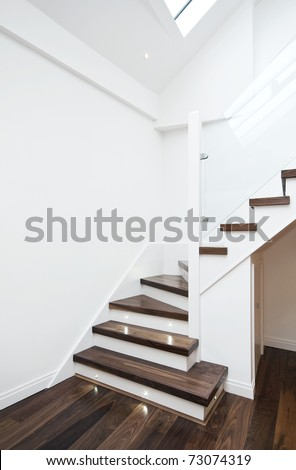 modern white staircase with wooden floor and glass barrier
