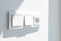 Modern White switch board with two switch and one european plug. European electrical outlet. Selective focus