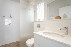 Modern white tiled bathroom with glass divided shower, hand basin and toilet, with decorative items and window