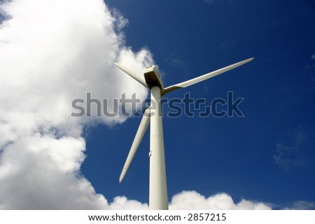 Modern white wind turbine or wind mill producing energy to power a city