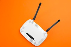 Modern Wi-Fi router on orange background, top view