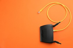Modern Wi-Fi router on orange background, top view. Space for text