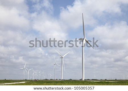 Modern Wind Energy Turbine Power Station under Blue Sky with Clouds. - stock photo