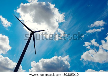 Modern wind energy turbine power station under blue sunny sky with many clouds