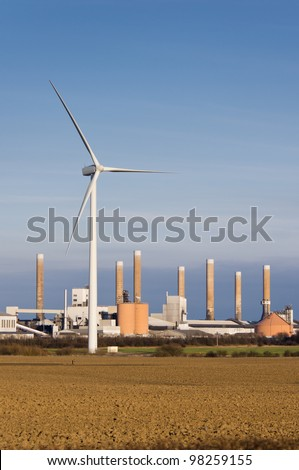 Modern wind turbine with old factory behind it vertical