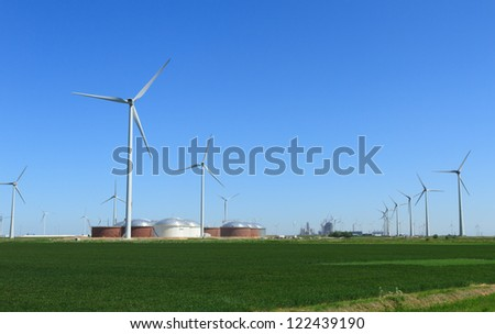 Modern wind turbines, fuel storage tanks and industry in the Eemshaven, Holland.