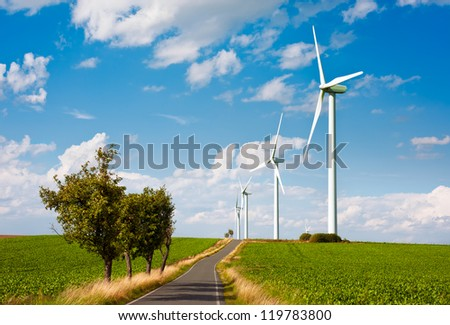 Modern wind turbines over green fields and a road
