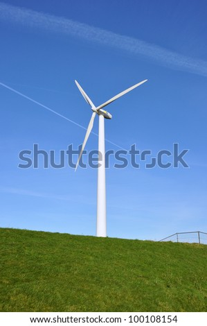 Modern windmill in the water behind a green grassy dike