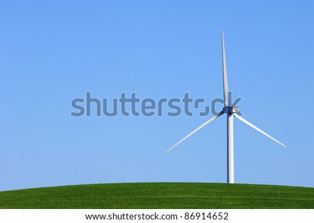 Modern windmill with blue sky in a green meadow