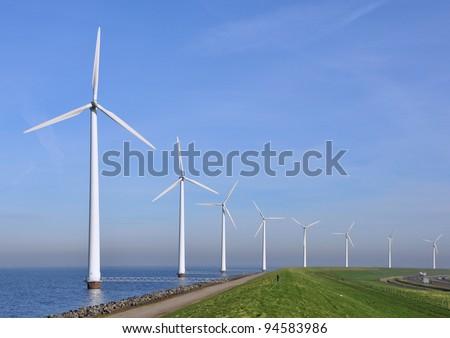 Modern windmills in the water near the shore along a green grassy dike