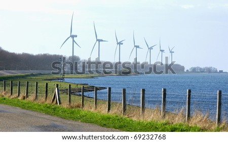 Modern windtrubines in a landscape by the water