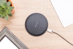 "Modern wireless charger for devices, phones and electronics. Smart phone charger on a table, with inscription ""Wireless charger"" on the top."