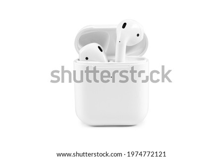 Modern wireless earbuds headphones lying in a charging case isolated on white background.  Stock photo ©