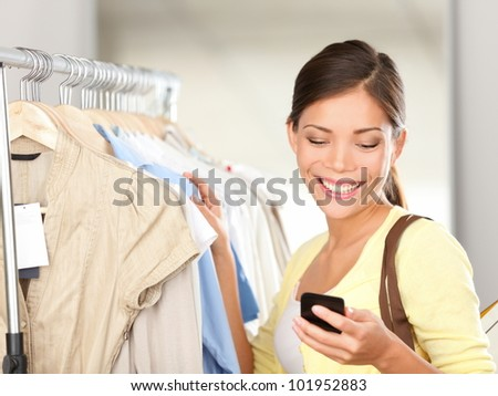 Modern woman shopping looking at smartphone texting or talking smiling happy in clothes store. Beautiful young mixed race Asian / Caucasian young woman shopper.