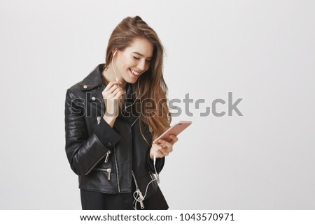 Modern woman with urban style in touch with technology. Attractive european female with blonde hair wearing leather jacket, holding smartphone, listening music in earphones, enjoying using new phone