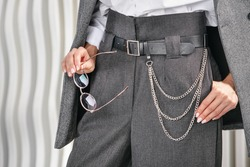 Modern women's business suit. Gray women's business trousers, with a high waist and a chain on the belt. A fragment of the model's body in a blazer, trousers and a white shirt.