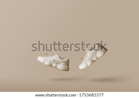 Modern women's sneakers of light color flying on a beige background. Stylish fashionable minimalism, concept levitation shoes, creative layout with copy space for text.